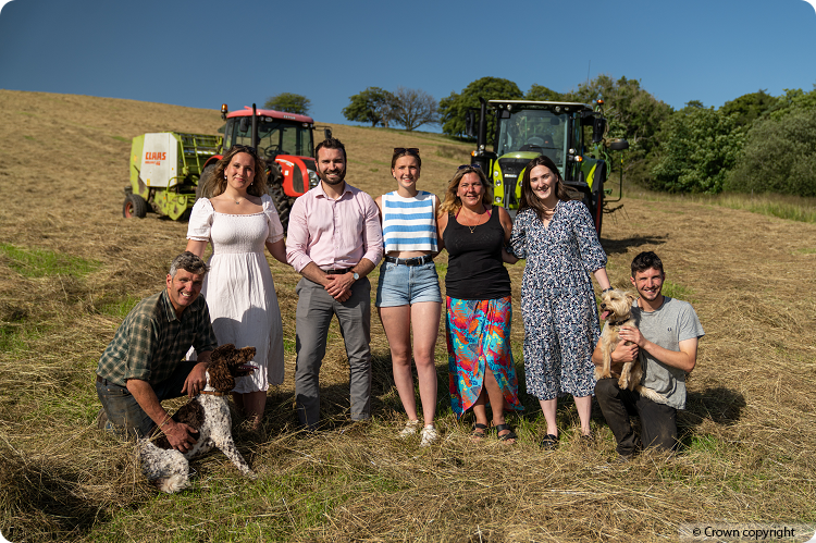 The Imrie family from Torrance near Glasgow gathered together in a hay field with two tractors parked in the background.
