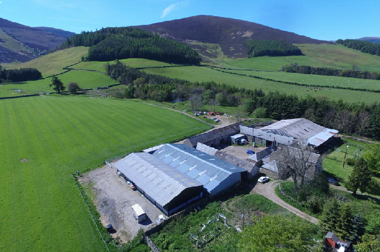 Aerial photo of Hundleshope Farm with the steading in the foreground and the land rising up to a hill in the distance with a bright blue, cloudless sky behind it.